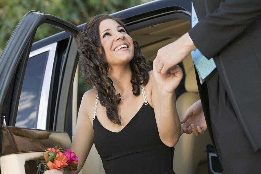 Well dressed teen getting out of limo for prom