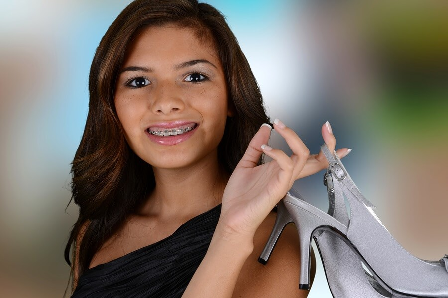 Smiling teen holding high heels on prom night