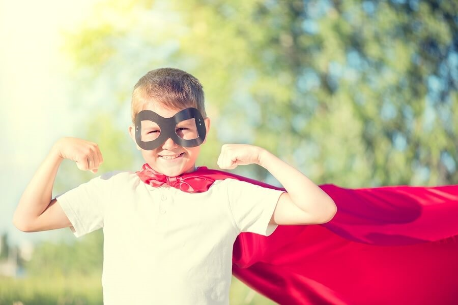 Happy Kid Wearing Cape and Mask Showing Muscles
