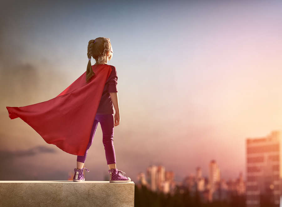 Young superhero girl wearing a cape and standing proud