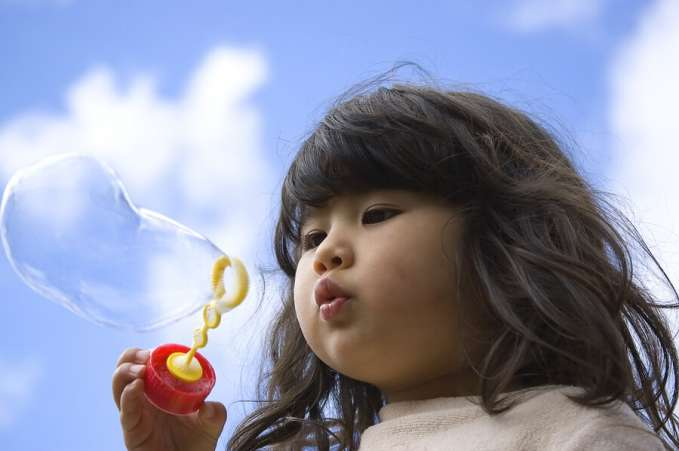 menina soprando bolhas