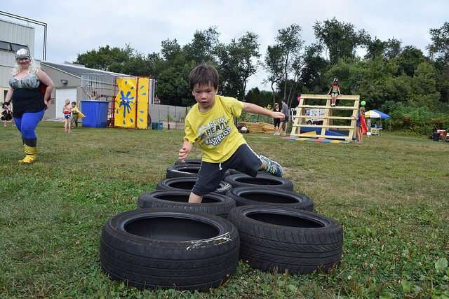Young boy running through tire obstacle course