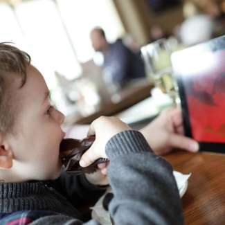 child using ipad while dining out