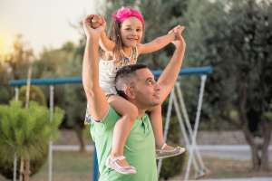 dad carrying daughter on shoulders