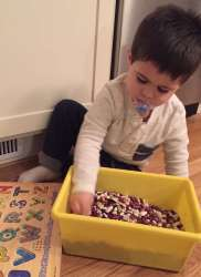Young Child Playing with a Bucket of Dried Beans