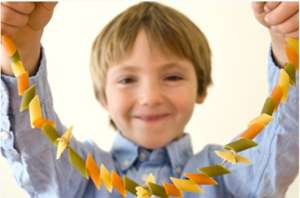 Kid holding macaroni necklace craft