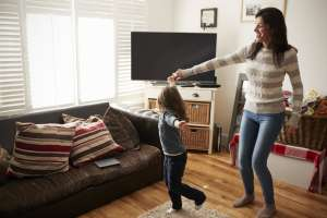 single mother and child dance in the living room