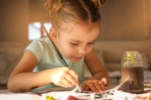 little girl stays busy doing crafts over school vacation