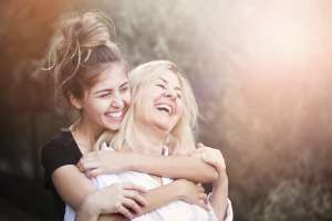 smiling adult daughter hugs mother