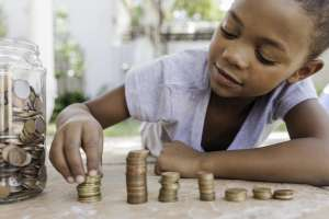 child learning the importance of saving money and budgeting