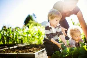 family celebrates earth day by working in the garden