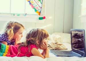 kids mindlessly watching something on a computer or tablet