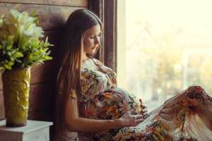 pregnant woman sitting in window