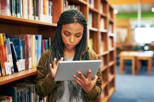 teenager looking at tablet in library