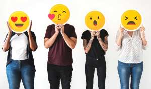 Diverse people holding emoji masks over face