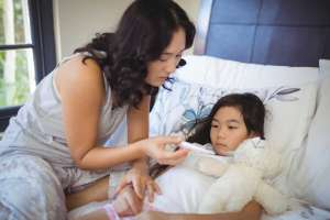 Mother checking body temperature of sick daughter