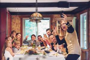 family taking selfie at thanksgiving dinner table