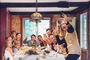 family taking selfie at thanksgiving dinner table