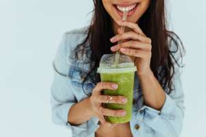 young woman drinking fresh juice smoothie