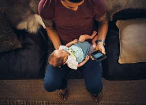 dad with newborn baby and smart phone