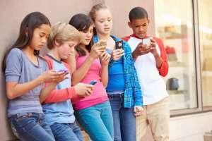 group of kids with smartphones vs. flip phones
