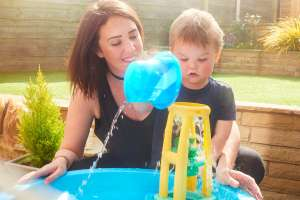 mom and son playing water table activity