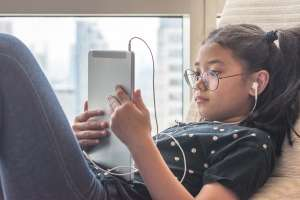 young girl using potentially dangerous apps on ipad
