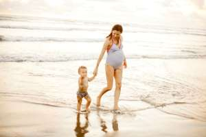 Pregnant woman playing with her son on the beach