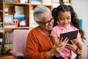 A child playing on an ipad with her grandmother