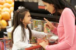 mom disciplining daughter in store