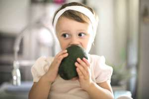 little girl biting avocado as part of keto diet