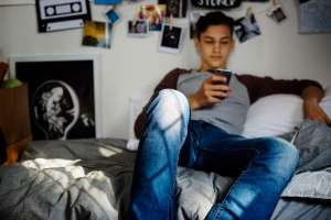 Boy with chronic illness in college dorm scrolling on his phone