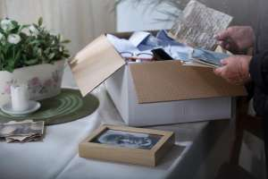 woman looking through box of family heirlooms to pass down