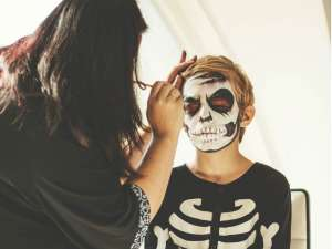 woman applying halloween makeup on kid
