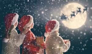 3 kids looking at Santa and his reindeer under moonlight sky.
