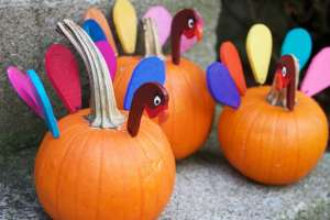 3 pumpkins decorated to look like turkeys for Thanksgiving kids table