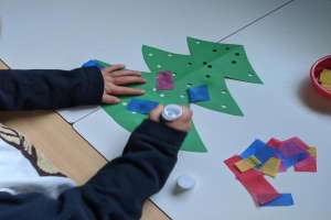 Young girl pasting tissue paper to paper Christmas tree