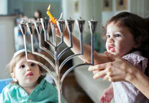kids lighting Hanukkah menorah