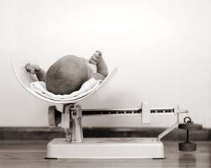 newborn baby being weighed on scale