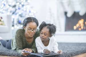Mom reading kwanzaa book to her daughter