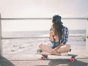 VSCO girl teen on skateboard at beach