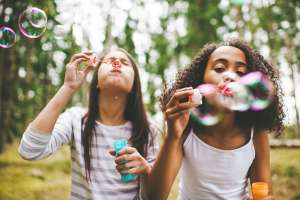 Two girls blowing with bubbles gifts