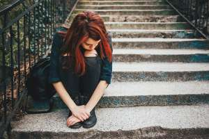 Burnt out teen girl sitting alone on outside steps
