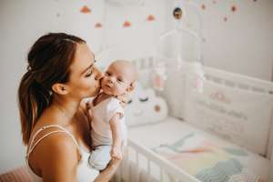 Mother tenderly holding newborn baby girl with popular 2019 baby name