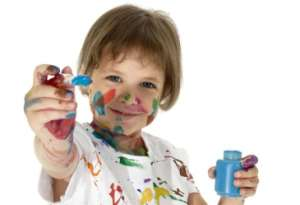 Little girl holding paint brush while covered in paint