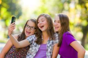 tween girls taking selfie with smartphone