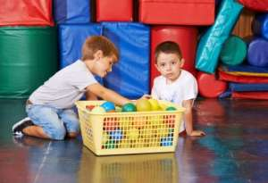 Two boys cleaning up toys in gym class