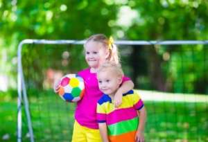Two young kids playing soccer outside