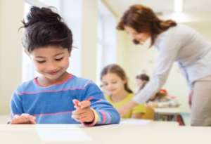 Smiling Little Girl holding Pen and Writing on Paper