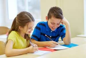 Two Smiling Students Writing in Notebooks
